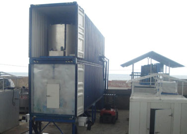Containerized flake ice machine with rake ice storage room